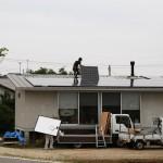屋根に太陽光パネルを設置中です。